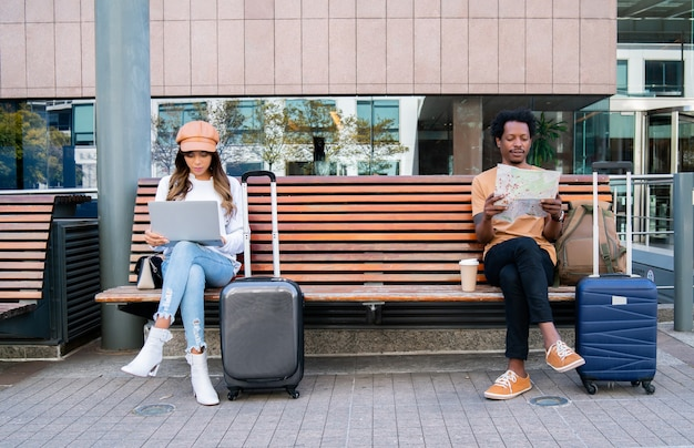 Retrato de um casal de turistas sentado no banco do lado de fora do aeroporto ou da estação ferroviária. mulher usando laptop e homem olhando para o mapa