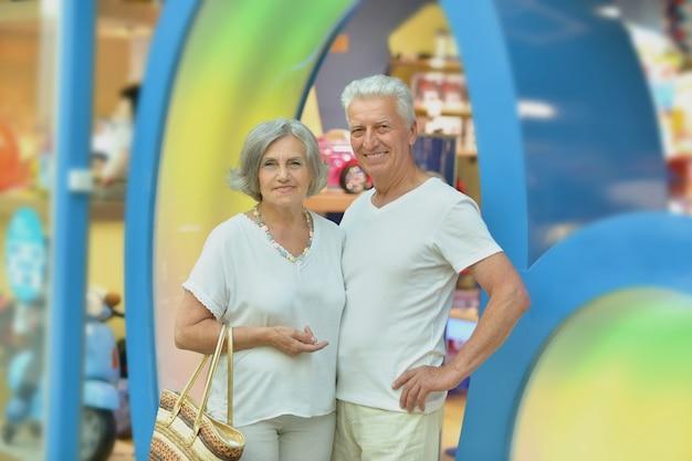 Retrato de um casal de velhos divertido em um shopping