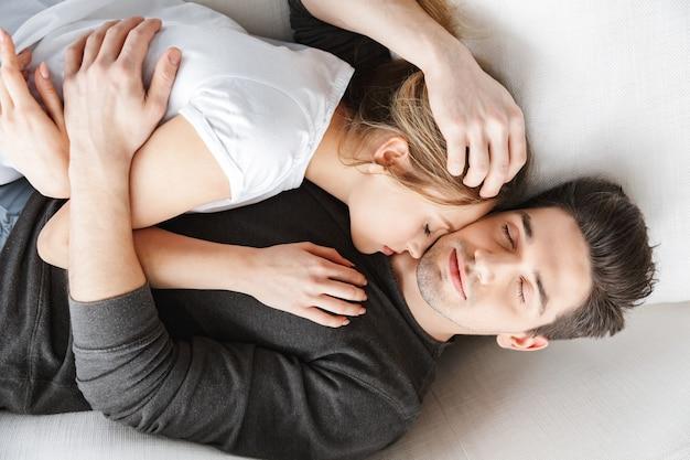 Retrato de um casal encantador, homem e mulher se abraçando enquanto estava deitado no sofá em uma sala iluminada em casa