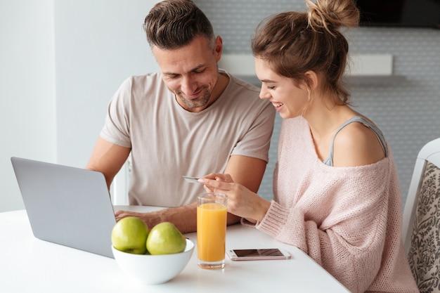 Retrato de um casal feliz, compras on-line com laptop