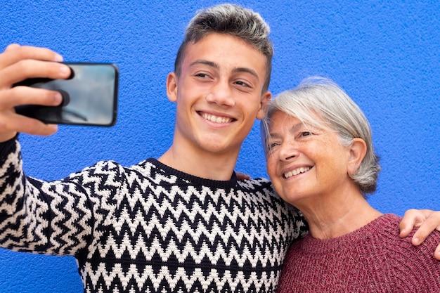 Retrato de um casal feliz de avó e neto adolescente, sorrindo e se abraçando, olhando para o celular para uma selfie. fundo de parede azul