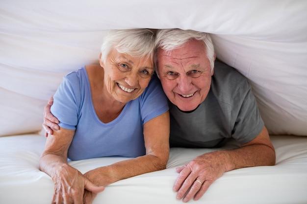 Retrato de um casal feliz de idosos embaixo do cobertor, na cama do quarto