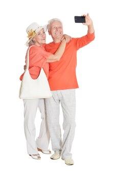 Retrato de um casal feliz de idosos fazendo selfie em fundo branco