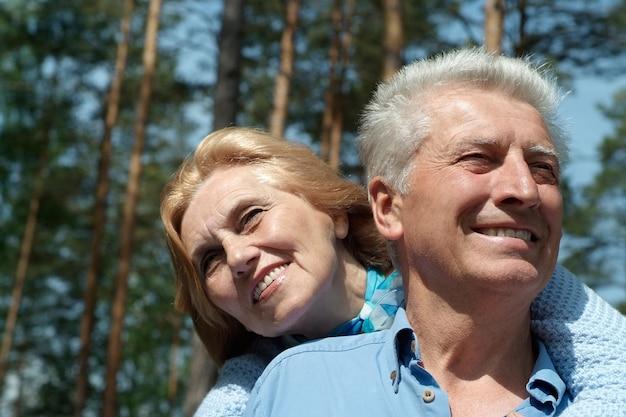 Retrato de um casal feliz de idosos na floresta de outono