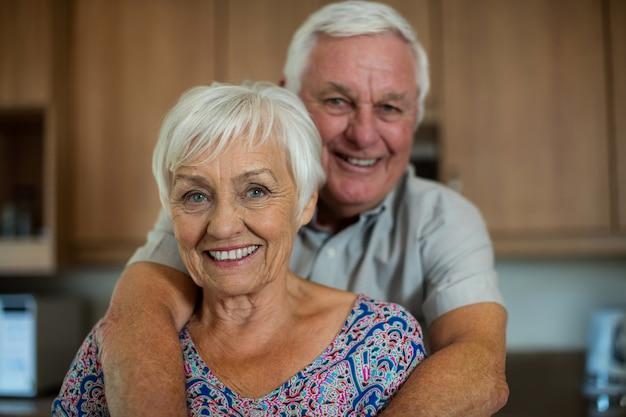 Retrato de um casal feliz de idosos se abraçando na cozinha de casa