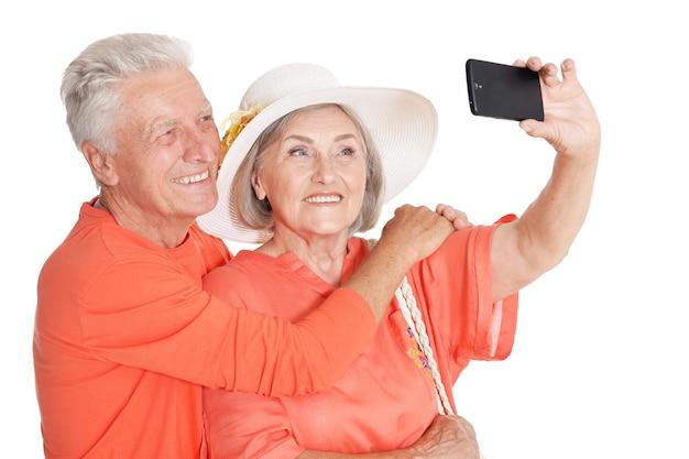 Retrato de um casal feliz de idosos tirando uma foto de selfie em fundo branco