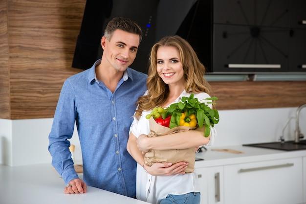 Retrato de um casal feliz em pé na cozinha com um saco de papel com legumes frescos