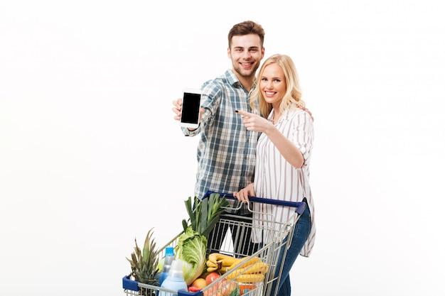 Retrato de um casal feliz, mostrando o telefone móvel de tela em branco