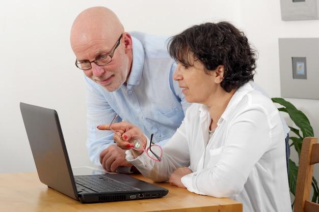 Retrato de um casal feliz sênior usando laptop