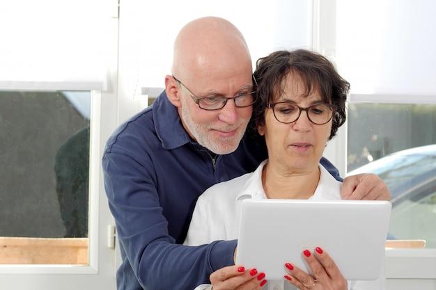 Retrato de um casal feliz sênior usando tablet digital