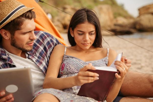 Retrato de um casal feliz sentado na barraca usando um tablet e lendo um livro