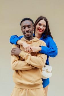 Retrato de um casal interracial feliz em roupas casuais jovem morena de aparência europeia abraça seu namorado afro-americano