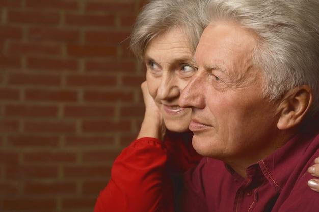 Retrato de um casal maduro perto de uma parede na rua