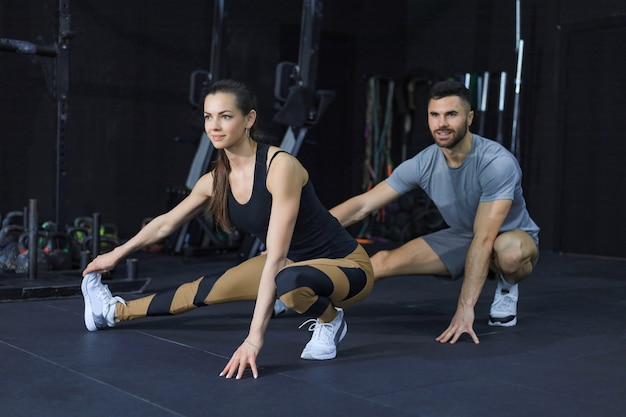Retrato de um casal musculoso fazendo alongamentos nas pernas
