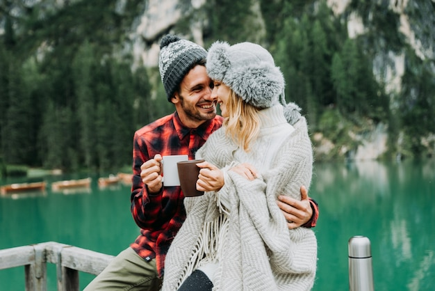 Retrato de um casal romântico de adultos visitando um lago alpino em braies itália no inverno