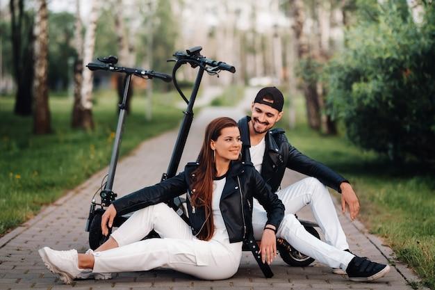 Retrato de um casal sentado perto de scooters elétricos, curtindo o tempo juntos na natureza, dois amantes em scooters elétricos