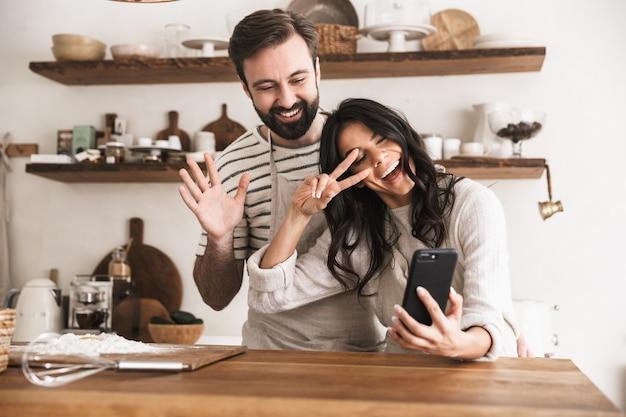 Retrato de um casal sorridente, homem e mulher de 30 anos, usando aventais, se abraçando e segurando o smartphone enquanto cozinham na cozinha de casa