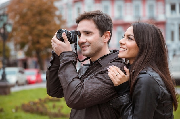 Retrato de um casal sorridente, viajando e fazendo foto na frente na velha cidade europeia