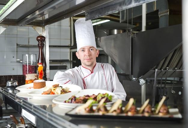 Retrato de um chef com comida cozida na cozinha no restaurante.