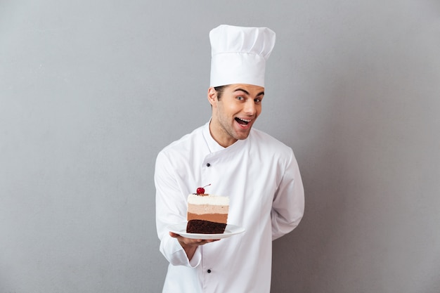 Retrato de um chef masculino animado sorridente, vestido de uniforme