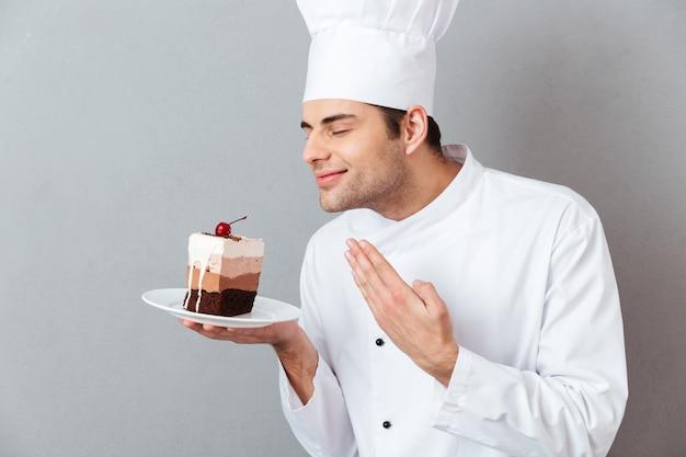 Retrato de um chef masculino satisfeito, vestido de uniforme