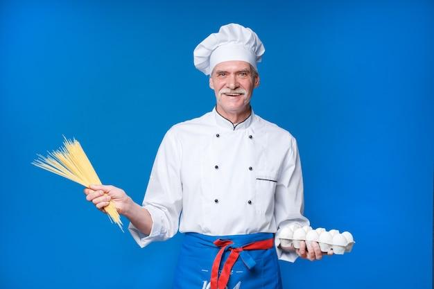 Retrato de um chef profissional e sorridente feliz segurando macarrão com ovos nas mãos