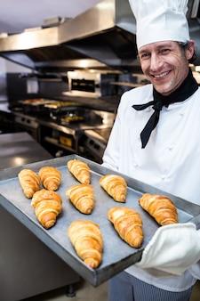Retrato de um chef segurando a bandeja de croissants