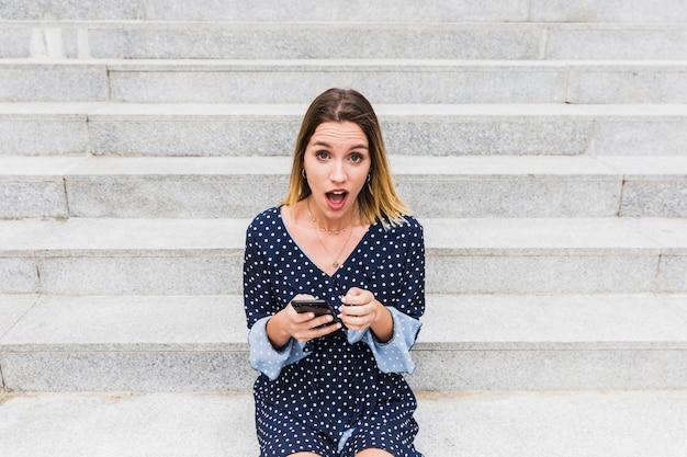 Retrato, de, um, chocado, mulher sentando, ligado, escadaria, segurando telefone móvel