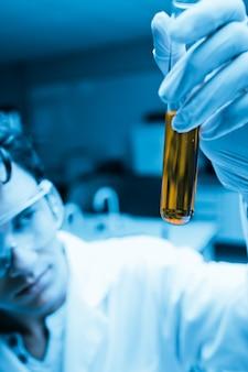 Retrato de um cientista masculino olhando um tubo de ensaio