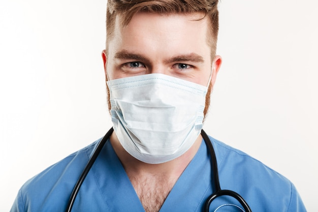 Retrato de um cirurgião masculino concentrado usando estetoscópio e máscara