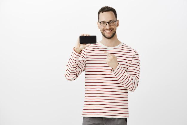 Retrato de um cliente fofo e satisfeito e impressionado com cerdas em óculos pretos da moda