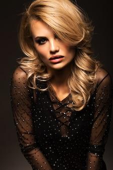 Retrato de um close-up loiro lindo em um preto