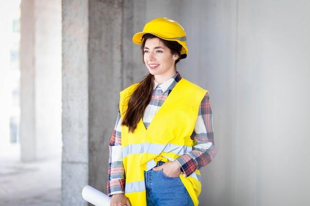 Retrato de um construtor de mulher jovem sorridente com desenhos na mão