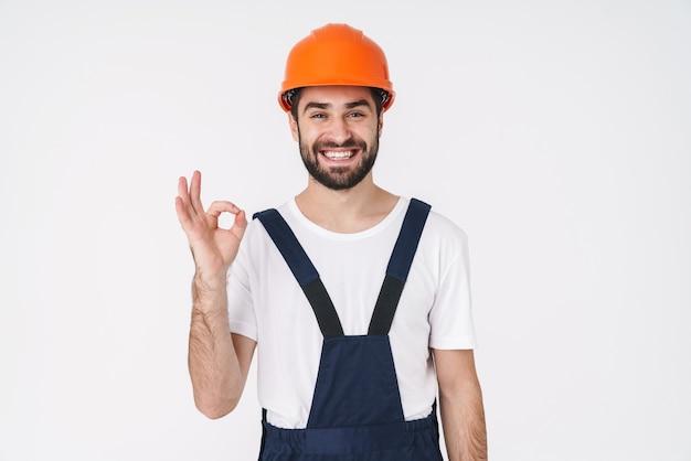 Retrato de um construtor jovem positivo em capacete posando isolado sobre uma parede branca, mostrando o gesto certo.