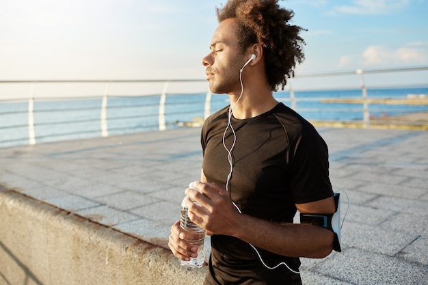 Retrato de um corredor afro-americano com os olhos fechados após o treinamento cardiovascular, vestindo uma camiseta preta com fones de ouvido e uma garrafa de água mineral nas mãos. relaxar depois de correr à beira-mar