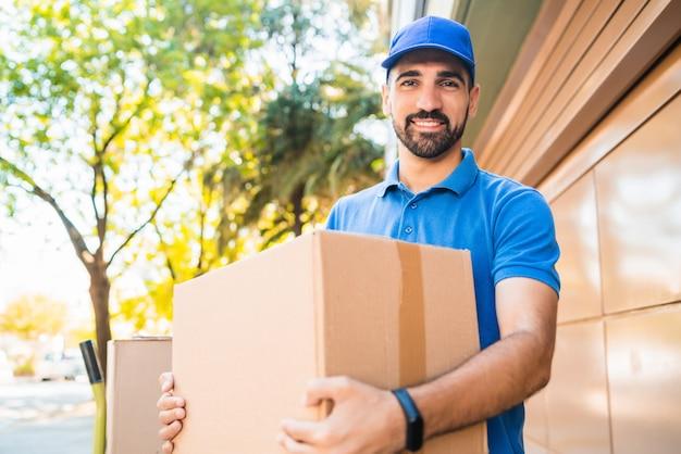 Retrato de um correio entregador com caixas de papelão nas mãos ao ar livre. entrega e conceito de envio.
