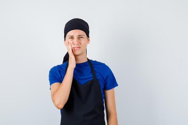 Retrato de um cozinheiro adolescente do sexo masculino sofrendo de dor de dente, vestindo camiseta, avental e parecendo dolorido com a vista frontal