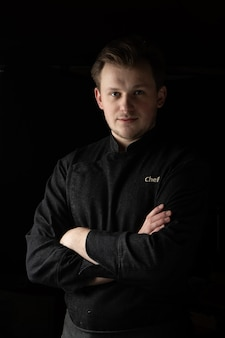 Retrato de um cozinheiro chefe com uma jaqueta em um fundo escuro