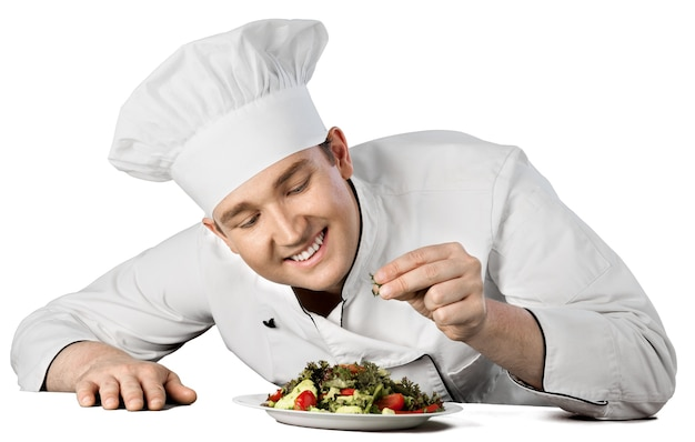 Retrato de um cozinheiro chefe masculino preparando salada isolada em um fundo branco
