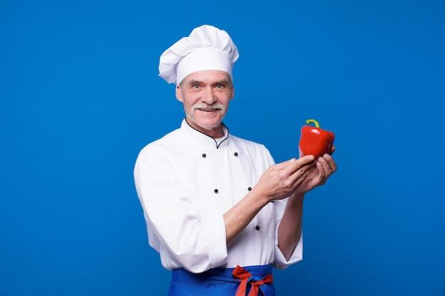 Retrato de um cozinheiro chefe sênior sorridente segurando pimenta vermelha isolada em uma parede azul