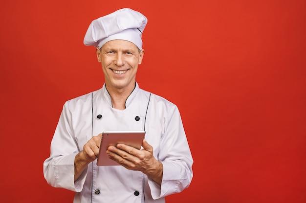 Retrato de um cozinheiro de sorriso superior de sorriso do cozinheiro chefe que mantém o tablet pc isolado em um fundo vermelho.