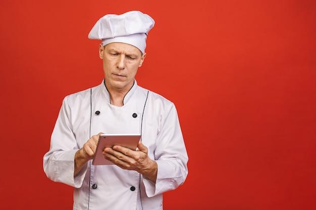 Retrato de um cozinheiro de sorriso superior sério do cozinheiro chefe que mantém o tablet pc isolado em um fundo vermelho.