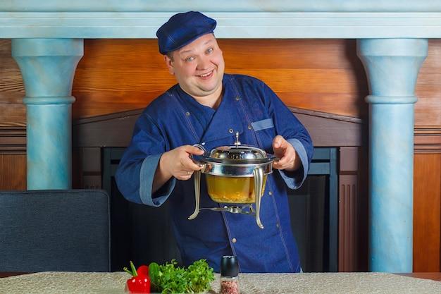 Retrato de um cozinheiro masculino do cozinheiro chefe que guarda a bandeja. conceito de utensílios de cozinha.