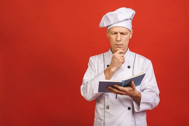 Retrato de um cozinheiro masculino sênior feliz do cozinheiro chefe que mantém o livro da receita e que prepara o alimento isolado em um fundo vermelho.