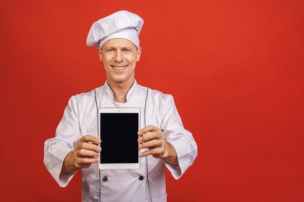 Retrato de um cozinheiro masculino sênior feliz do cozinheiro chefe que mostra a tela de tablet pc vazia isolada em um fundo vermelho.