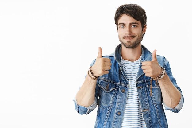 Retrato de um cusomer masculino bonito e satisfeito com olhos azuis e cerdas em jaqueta jeans mostrando polegares para cima e sorrindo satisfeito, expressando opinião positiva sobre o produto