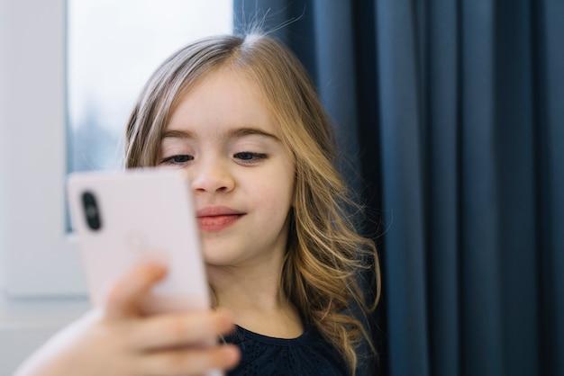 Retrato, de, um, cute, menina, levando, selfie, com, telefone móvel