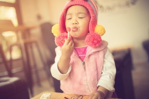 Retrato, de, um, cute, menininha, em, um, cor-de-rosa, vestido, comer, um, luminoso vermelho, pirulito, ficar
