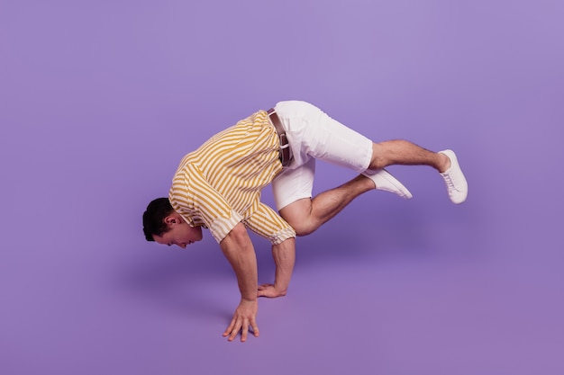 Retrato de um dançarino moderno, dançar hip hop legal, mexer e ficar de mãos dadas no fundo roxo