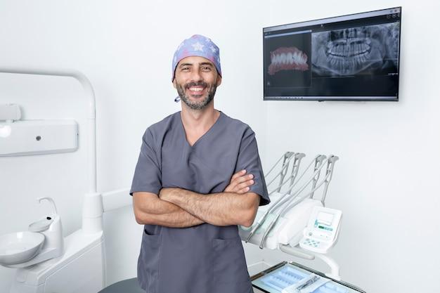 Retrato de um dentista de uniforme e boné protetor em pé com os braços cruzados em uma clínica odontológica